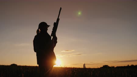 enstrüman : Silhouette of a woman with a rifle. A sieve in the field at sunset. Sports shooting concept. Back view