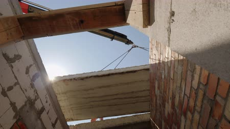 eixo : A crane installs a floor panel in a multi-storey building, a bottom view Stock Footage
