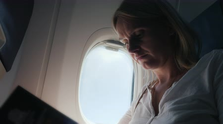 paper airplane : Portrait of a woman flipping through a magazine in an airplane