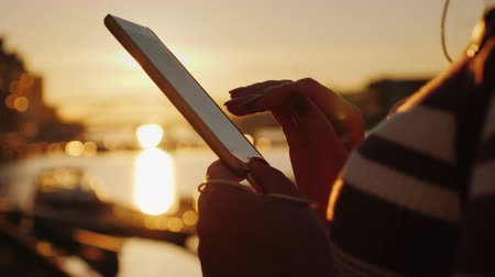 göğüs : Hands of a woman with a smartphone on the background of a pier with yachts at sunset