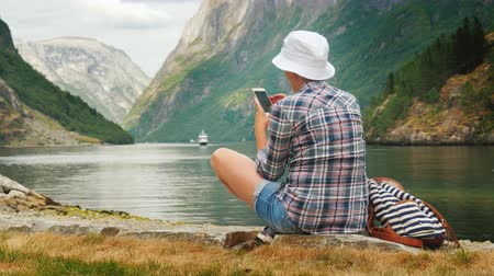 aventura : A woman uses a smartphone on the shore of a picturesque fjord in Norway. Always in touch, technology on the road