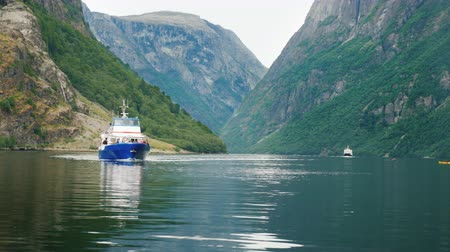 scandinavisch : A small cruise ship sails along the picturesque fjord in Norway. Travel and tourism in Scandinavia