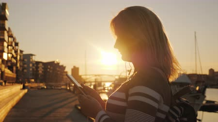 beautifully : A woman in headphones uses a smartphone on the pier on the background of private yachts. At sunset, the sun beautifully illuminates it.