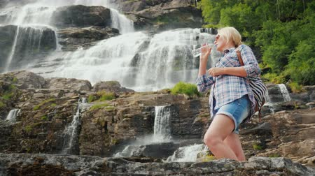 tvindefossen : Active woman drinks clean water against the background of the Twindefossen waterfall in Norway