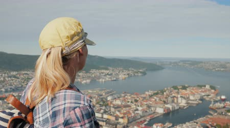 hayran olmak : A woman tourist admires a beautiful view of the city of Bergen in Norway