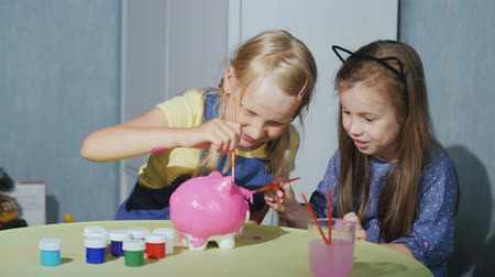 гуашь : Two girls girlfriends paint a piggy bank together, have fun