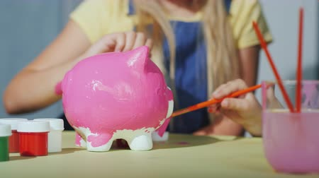 гуашь : Children paint the piggy bank with pink paint. In the frame are visible only hands