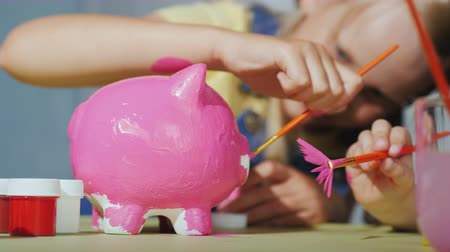 гуашь : Children cheerfully paint piggy bank. Happy childhood concept