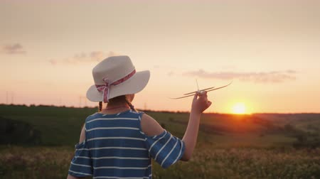 objektiv : A fun little girl with a straw hat with pigtails launches a toy airplane in the sky.