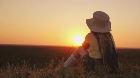 insult : A child in a hat sits on a hill, admiring the sunset Stock Footage