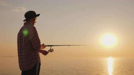 fishing pole : A young man is fishing on the shore of a picturesque lake at sunset. Side view