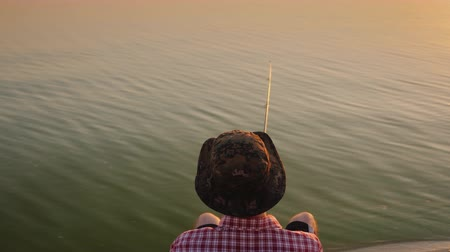fishing pole : Top view: A teenager in a hat sits on a chair by the lake and catches fish with a fishing rod