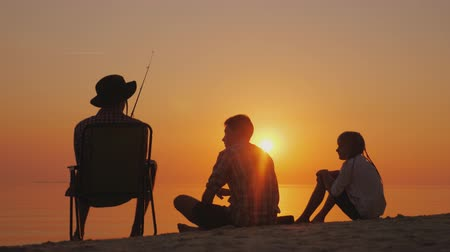 fishing pole : Three teenagers are fishing on the shore of the lake at sunset. Happy childhood concept