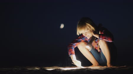 ищу : A girl with a flashlight in her hand is looking for something on the beach in the dark. Research and adventure concept Стоковые видеозаписи