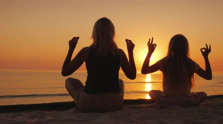 filha : Mom and daughter are meditating by the sea at sunset. Health and happy time together
