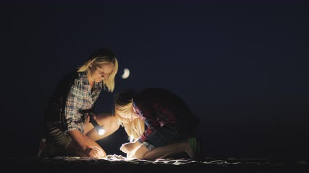 scoprire : Mom and daughter are playing together in the sand at night. They shine with a flashlight looking for something. Adventure and a happy time together
