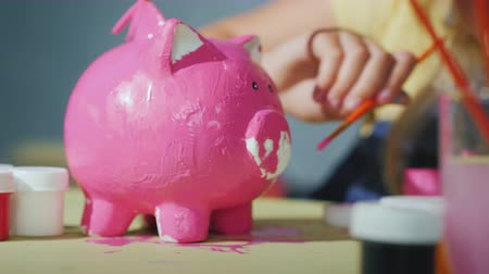 porquinho : Children together paint a piggy bank in pink. Games with children concept