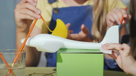 гуашь : Childrens hands with brushes paint the model of the aircraft. Developing games with children
