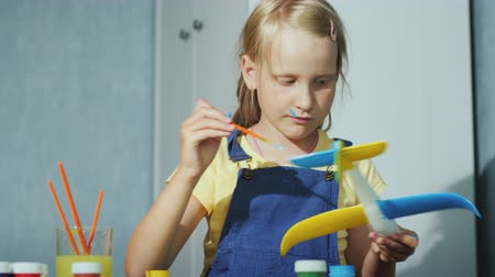 гуашь : A blonde girl paints a model airplane. Educational activities for children