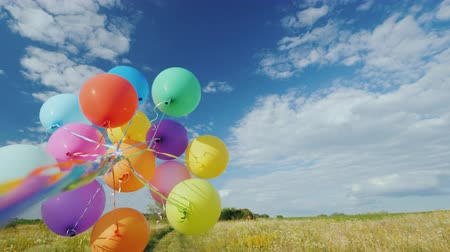 резина : The wind plays with a group of balloons against a beautiful green meadow