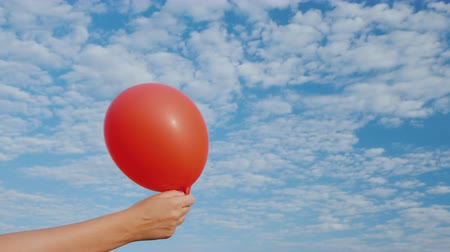 düşük : Air comes from the red air balloon and it becomes limp. Against the background of the blue sky