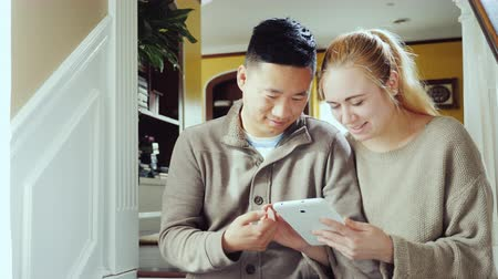 ırklararası : Asian man and Caucasian woman sitting side by side on stairs at home. Use a tablet