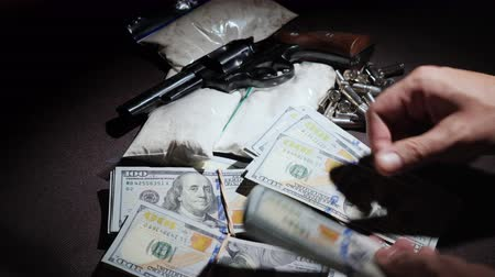 пистолеты : Dirty money - a man counts up cash dollars in a usa with weapons and drugs Стоковые видеозаписи