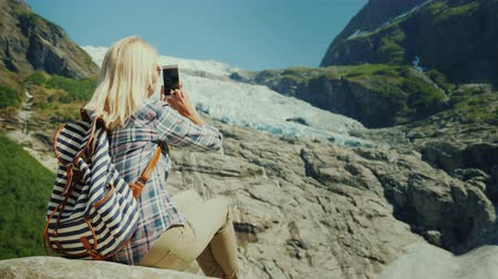 용기있는 : Woman tourist taking pictures of the glacier. Traveling in Norway concept 무비클립