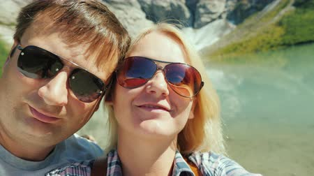 relieves : Young couple relieves himself on the video on the background of mountains and glacier in Norway. Journey through Scandinavia Stock Footage
