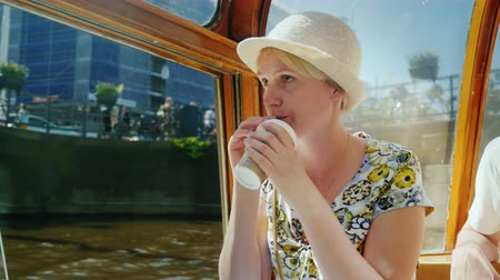 arka görünüm : A woman tourist sails on a cruise boat along the canal of Amsterdam, drinks coffee Stok Video
