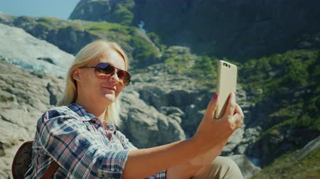 ledovec : A happy tourist does selfie on the background of a glacier in Norway Dostupné videozáznamy