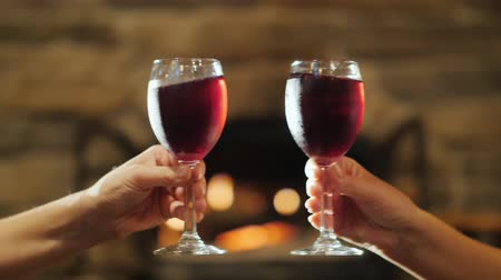 na zdraví : Two hands with glasses of red wine. Clinking against the background of a burning fireplace, celebrating in a cozy house the concept Dostupné videozáznamy
