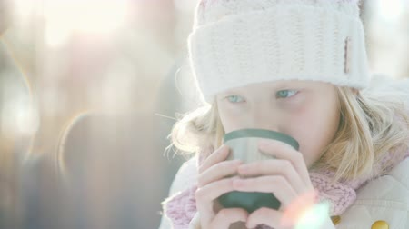 xale : A little girl in a warm knitted hat drinks hot tea from a flask in the winter forest. Portrait. Vídeos