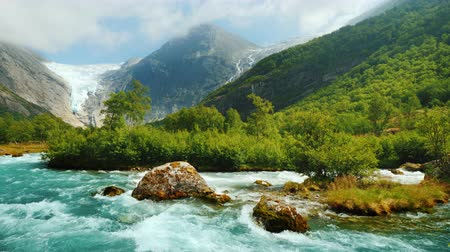 vários : Briksdal glacier with a mountain river in the foreground. The amazing nature of Norway