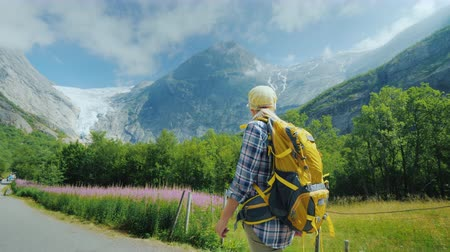 川岸 : A woman walks along the path to the Briksdal Glacier in Norway, a side view. Traveling in Scandinavia