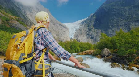 norweger : A woman traveler looks at the famous Briksdal glacier in Norway, a back view. Traveling in Scandinavia Videos