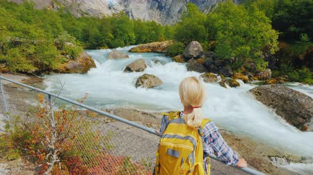 川岸 : A woman traveler looks at the famous Briksdal glacier in Norway, a back view. Tilt shot. Traveling in Scandinavia