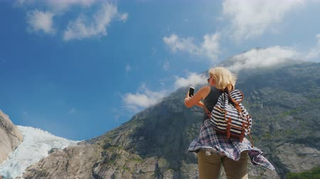 ledovec : An active young woman takes pictures of the famous Riksdal glacier. Popular and famous sights of Norway
