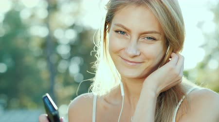 beautifully : Happy woman in headphones listens to music, uses a smartphone. The sun beautifully illuminates her hair Stock Footage