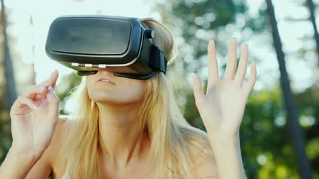 invisible : Attractive young woman is playing in the helmet of virtual reality. Touching invisible wall