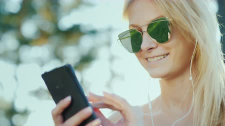 beautifully : Happy women in sunglasses use a smartphone. On vacation, the rays of the sun beautifully illuminate her hair