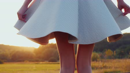 saia : A woman in a light skirt with slender legs turns around herself, the sun illuminates her clothes