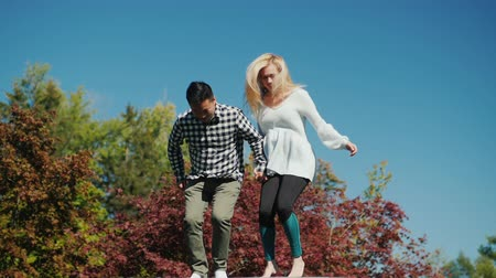 nevető : Young active couple jumping on a trampoline. Have a good time together. Outdoors activity