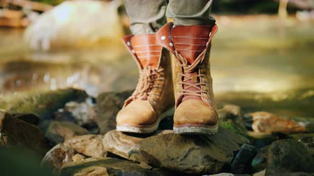 крайняя местности : A tourist in trekking boots stands near a mountain stream. Hiking and active rest