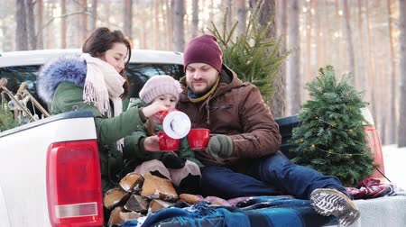 ピックアップ : Happy family of three people is drinking hot tea from a flask, sitting in the back of a car near the New Year tree in the winter forest