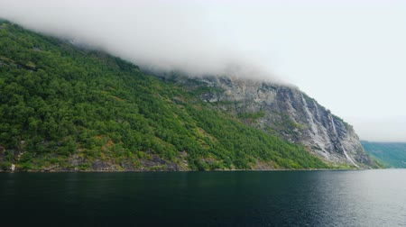 gömülü : Beautiful mountains, peaks are buried in fog and clouds. The beautiful nature of Norway, the view from a cruise ship that floats across the waters of the fjord