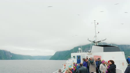 come : Geirangerfjorden, Norway, July 2018: A group of tourists on a cruise ship feeding gulls