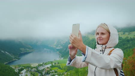 norweger : A happy tourist is photographed against the background of a picturesque fjord in Norway. It is worth on a popular photographic object - a flying cliff