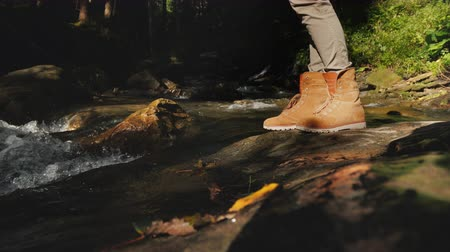 крайняя местности : A traveler in hiking boots passes through slippery stones. Only the legs are visible