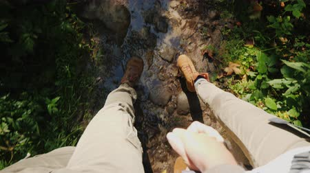 csúszós : A couple of tourists hold hands and walk on a slippery stony path in the forest. Only the legs are visible Stock mozgókép